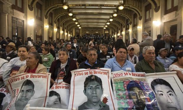 Meksiko Kenti'ndeki Ulusal Saray'da yapılan Cumhurbaşkanlığı Yemin Töreninde, aileler, zorla kaybettirilen genç, stajyer öğretmen oğullarının fotoğraflarını taşıdı. (Foto: Christian Palma/Associated Press-AP)
