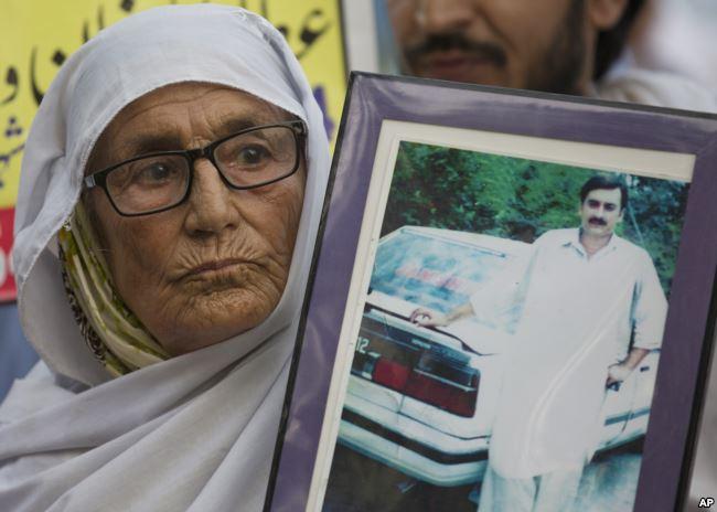 Pakistanlı bir anne Zorla Kaybettirme Mağdurları Uluslararası Günü'nde İslamabad'da yapılan buluşmalarda zorla kaybettirilen oğlunun resmini taşıyor.